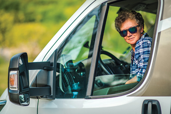 Woman driving RV looking out window